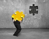 foto of insert  - Businessman carrying 3D gold jigsaw puzzle piece to insert the dark hole on concrete wall background - JPG