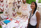 picture of blouse  - young Hispanic woman admiring embroidered white blouses in Mexican market  - JPG