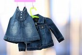 stock photo of denim wear  - Fashion baby denim dress with jacket hanging on a hanger - JPG
