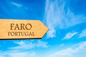 foto of faro  - Wooden arrow sign pointing destination FARO PORTUGAL against clear blue sky with copy space available - JPG