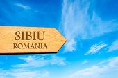stock photo of sibiu  - Wooden arrow sign pointing destination SIBIU ROMANIA against clear blue sky with copy space available - JPG