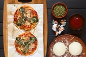 picture of oregano  - Homemade spinach and tomato pizza on baking paper on wooden board pizza dough dried oregano tomato sauce garlic on the side photographed overhead on dark wood with natural light - JPG
