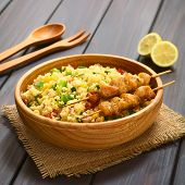 foto of sweet-corn  - Couscous salad made with bell pepper tomato cucumber red onion and sweet corn kernels served with baked chicken on skewer in wooden bowl - JPG