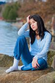 stock photo of off-shore  - Young unhappy biracial teen girl in blue shirt and jeans sitting on rocks along lake shore looking off to side resting head in hand and one knee raised - JPG