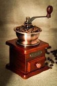 stock photo of wooden box from coffee mill  - Coffee bean grinder is on the burlap sack background. ** Note: Soft Focus at 100%, best at smaller sizes - JPG