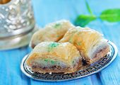 foto of dessert plate  - Baklava Turkish dessert on metal plate and on a table - JPG