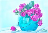 stock photo of bunch roses  - Bunch of small pink Roses in a glass vase over a wooden table - JPG