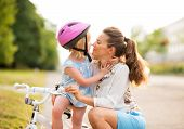 image of eskimos  - Eskimo kisses between a proud mother and daughter who has just learned how to ride her bicycle - JPG