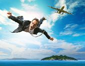picture of time flies  - business man flying from passenger plane over natural blue ocean island use for people holiday and vacation time to relaxing destination - JPG