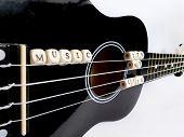 stock photo of ukulele  - Letters of beads on a black ukulele on a white background - JPG