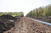 stock photo of loam  - A uncovered pipeline construction site with soil around - JPG