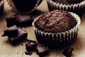picture of chocolate muffin  - chocolate muffins with chocolate slices on wooden background  - JPG