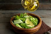 foto of pores  - Poring green salad with olive oil on wooden table - JPG