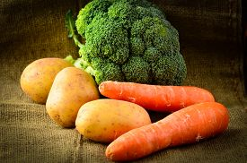 image of farmhouse  - Farmhouse Fresh Earthy Vegetables on a rustic hessian background, carrots, broccoli and potatoes. ** Note: Shallow depth of field - JPG