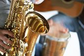 picture of saxophone player  - closeup of a saxophone player with drums and guitar in the background  - JPG