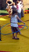 pic of childrenwear  - girl playing hula-hoop. happy child playing outdoor. leisure item. summer season. sunday