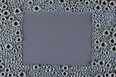 A Bunch Of Screw Nuts On A Gray Background poster
