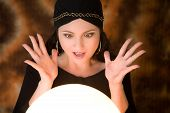stock photo of fortune-teller  - Fortune teller looking very surprised at what she is seeing in her cristal ball - JPG