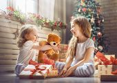 Merry Christmas and Happy Holidays! Cheerful cute childrens girls opening gifts. Kids wearing pajama poster