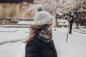 Stylish Hipster Woman In Knitted Hat Standing In Snowy City Street. Beautiful Fashionable Girl In Wa poster