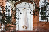 Beautiful And Delicate Lace Wedding Dress Hanging On The Door Of A Country House. Wedding Details. W poster