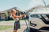 Cute Preschool Little Caucasian Girl Washing Car On Driveway In Front House On Sunny Summer Day. Kid poster