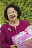 stock photo of early 60s  - Senior Woman with Gift - JPG