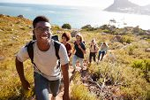 Millennial African American man leading friends hiking single file uphill on a path by the coast poster