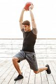 Picture of a strong serious concentrated young sports man outdoors at beach make exercises with ball poster