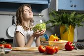 Young Cheerful Girl Prepares A Vegetarian Salad In The Kitchen, She Smells The Aroma Of The Finished poster