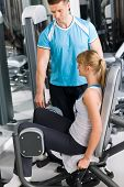 foto of personal trainer  - Young woman with personal trainer exercise legs at gym - JPG