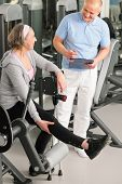 stock photo of physical therapist  - Physical therapist male assist active senior woman exercise at gym - JPG