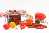 Sun-dried Tomatoes With Olive Oil In Glass Jar, Surounded With Fresh And Dry Tomatoes, Rosemary, Pep poster