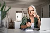 Happy senior woman using mobile phone while working at home with laptop. Smiling cool old woman wear poster