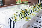 A Beautiful Banquet Table In Veranda Decorated With Flowers And Whole Lemons poster