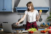 Young Beautiful Girl Prepares A Vegetarian Salad In The Kitchen And Looks Into A Laptop, She Learns  poster