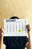 A Woman Holding November 2019 Calendar With 28th November Thanksgiving Day Marked With Marker poster