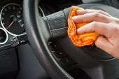 stock photo of steers  - polishing the car interior steering wheel with yellow duster - JPG