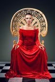 stock photo of throne  - A woman in a luxurious red dress sitting on a golden throne - JPG