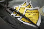 stock photo of wiper  - Close up of parking ticket placed under windshield wiper of a car - JPG
