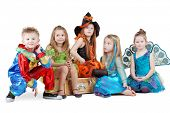 stock photo of witch ball  - Children in carnival costumes sit on chest and on floor near it - JPG