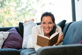 foto of bookworm  - Smiling woman resting reading sofa learning leisure activity - JPG