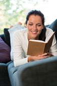 stock photo of bookworm  - Female student studying couch home bookworm woman living room - JPG