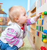 stock photo of child development  - little boy in the classroom early development plays with numerous bright toys - JPG
