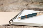 image of fountains  - Old golden fountain pen on blank notebook - JPG