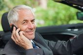 Cheerful businessman on the phone driving expensive cabriolet on sunny day