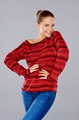 picture of flirtatious  - Sexy stylish young woman in a knitted red jersey posing with her hands on her hips giving the camera a playful flirtatious smile - JPG