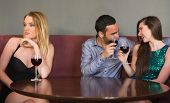 stock photo of beside  - Blonde woman feeling alone as two people are flirting beside her in a nightclub - JPG