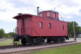 stock photo of caboose  - A vintage red wooden caboose on track - JPG