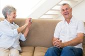 Retired woman taking photo of her partner on the couch at home in living room
